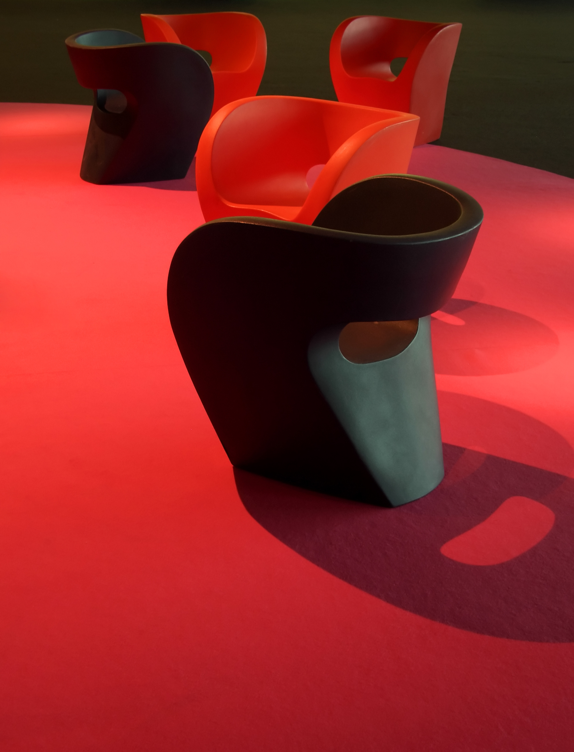 Several red and black plastic design couches on red magenta carpet with strong lighting